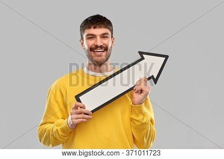 direction and people concept - happy smiling young man holding big white thick upwards arrow pointing to right over grey background