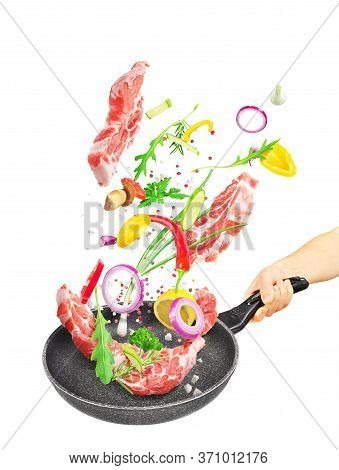 Cooking Concept. Vegetables And Meat Are Falling On A Pan Isolated On White Background. Healthy Food