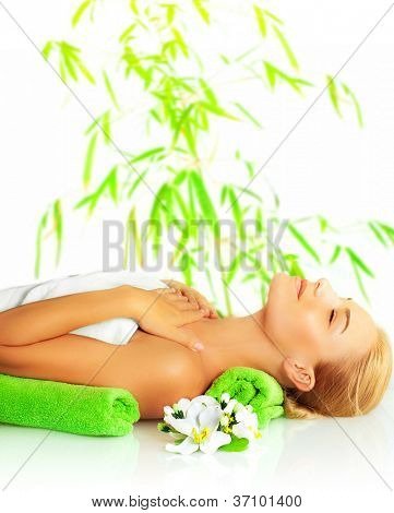 Picture of petty woman in spa salon, cute girl laying down on massage table, beautiful female enjoying dayspa, side view of young lady relaxed in spa over bamboo tree green leaves background