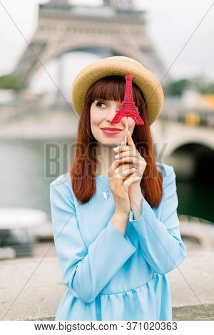 Beautiful Woman With Sweet Candy Lollipop Posing On The Background Of Eiffel Tower And Seine River.