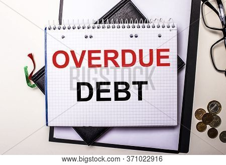 Overdue Debt Is Written In Red And Black Print In A White Diary With Coins And Glasses
