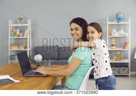 Lovely Girl Hugging Her Mom While She Working Online Via Laptop At Home. Cute Child Embracing Her Mo