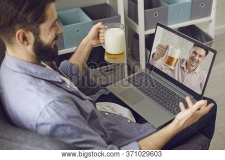 A Bearded Man With A Glass Of Beer Is Having Fun Talking With A Friend Using A Laptop Video Call At