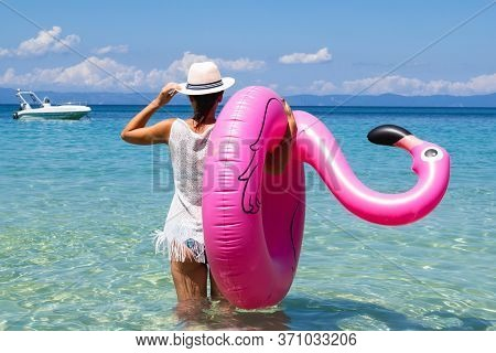 Stylish Pretty Woman On Summer Vacation On Tropical Beach Holding Inflatable Pink Flamingo Enjoying