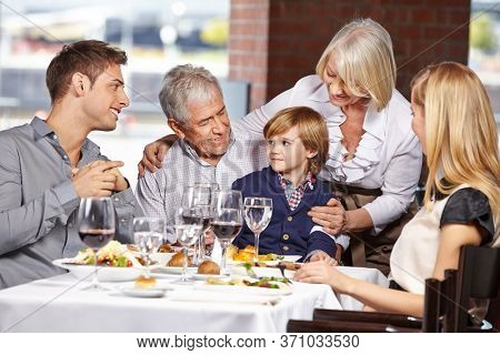 Happy family with three generations together in the restaurant