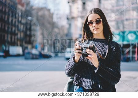 Hipster Girl In Sunglasses Fond Of Photography Using Vintage Camera Strolling On Showplaces