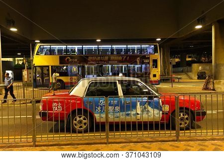 Hong Kong, China - October 6, 2018: Night View On Red Urban Taxi Cab Toyota Crown Comfort Is An Icon