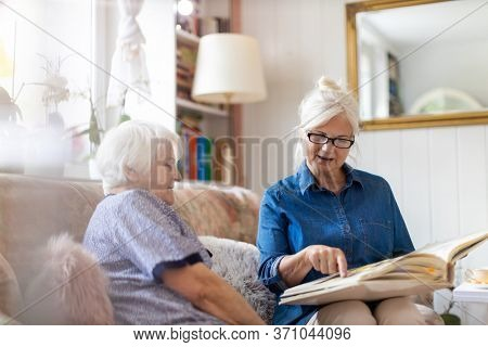 Senior woman and her adult daughter looking at photo album together on couch in living room