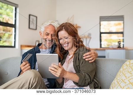 Happy mature couple sitting on sofa and doing online shopping on digital tablet. Senior husband and smiling wife paying bills online. Middle aged couple doing online payment on laptop, copy space.
