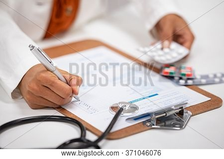 Closeup of woman hands writing medicine inventory. Close up hands of female doctor writing the medicine to be taken on the preoperative model sheet. Pharmacist checking inventory at hospital pharmacy.