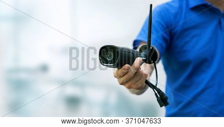 Security Cameras And Cctv Services Background - Man Holding Ip Camera In Hand With Copy Space