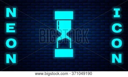Glowing Neon Old Hourglass With Flowing Sand Icon Isolated On Brick Wall Background. Sand Clock Sign