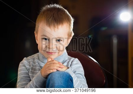 Facial Portrait Of Funny Joyfil Tricky Sly Smiling Pensive Blond Boy Over Dark Background With Speck