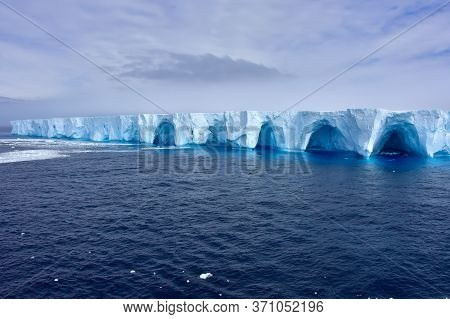 A Large Blue Iceberg Floating In Antarctica.