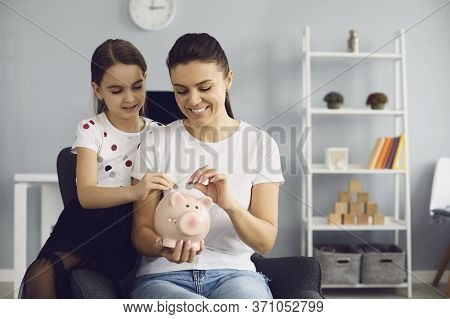 Young Mother And Her Daughter Saving Money At Home, Putting Coins Into Piggy Bank, Space For Text. E
