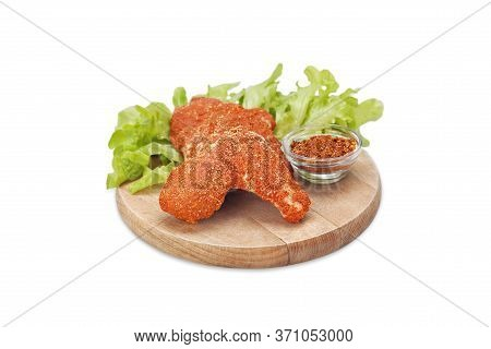 Raw Crispy Chicken Wings Breaded In Ground Chili Pepper And Bread Crumbs On A Wooden Board With Chil