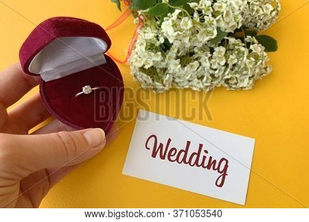 Wedding Ring In A Box And Flowers On A Yellow Background.wedding Photo.marriage Proposal To The Othe