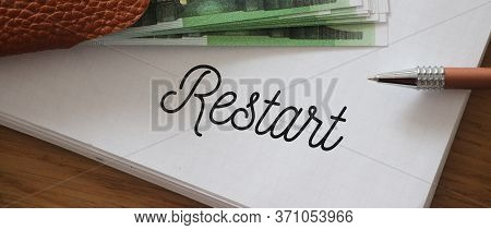 Restart Wrd On A Page Of Copybook And 100 Euro Bills. Business Rebranding Concept