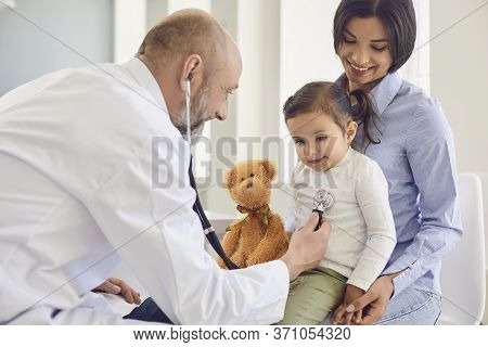 Family With A Visit To The Doctor In The Clinic Office. Senior Doctor With A Stethoscope Listens To