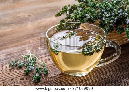 Herbal Tea With Thyme Over Rustic Wooden Background. Healthy Drink, Alternative Medicine, Antibacter