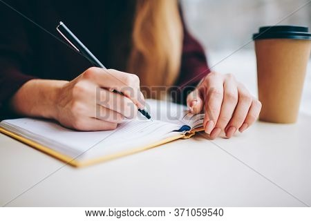 Female Student Writing Organisation Plan In Textbook For Education Using Pen For Making Notes