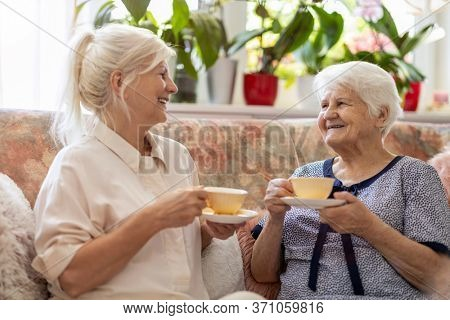 Senior Woman Enjoying a relaxing moment with her Daughter at Home