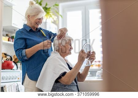 Woman cutting her elderly mother's hair at home