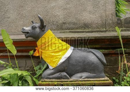 Large Carved Stone Cow Guardian Statue At Hindu Temple In Bali Indonesia. A Close Up On A Guardian F