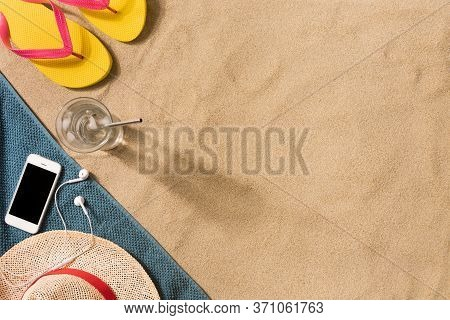 Summer Vacation Composition. Flip Flops, Hat And Glass Of Water On Sand Background. Travel Vacation