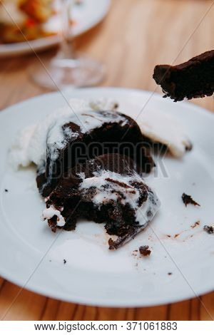 Chocolate Brownie With A Scoop Of Vanilla Ice Cream On A White Plate. Shokoladnyi Brownies For A Coo