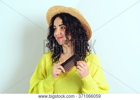Young Woman Combing Her Curly Hair At Home. Health Care And Beauty Concept. Stylish Woman With Long