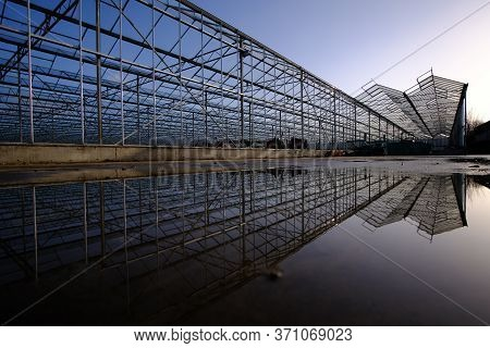 Structural Steel Structure Of A Greenhouse With Reflection Against A Clear Blue Sky In The Backgroun