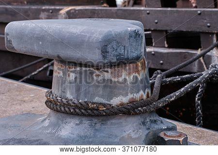 Large Black Mooring Bollard With Ropes Or Hawsers.