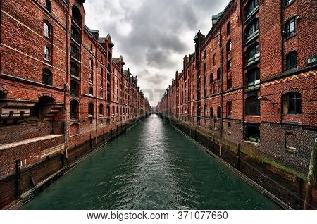 View Of A Canal In Hamburg Famous Old Speicherstadt Warehouse District Of Brick Buildings Stand On T