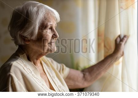 Senior woman looking out of window at home
