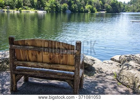 Empty Wooden Bench On The Shoreline Of Mohonk Lake, In Upstate New York.