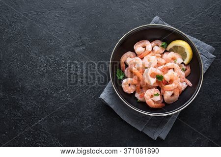 Shrimps (prawns)  In Bowl On Black Background. Fresh Seafood Ingredient - Shrimp Tails. Boiled Prawn