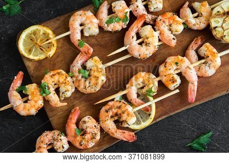 Grilled Shrimp Skewers. Seafood, Shelfish. Shrimps Prawns Skewers With Herbs, Garlic And Lemon On Bl