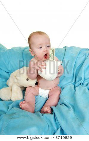 Bebé sosteniendo una alcancía con billete de 100 dólares