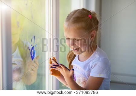Portrait Of A Happy Little Girl Draw Palms On The Window. Painted Children's Hands Leave A Mark On T