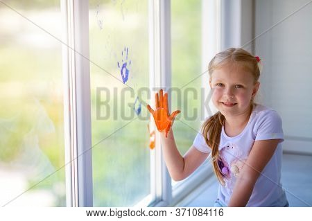 Children Girl Draw With Palms On The Window. Painted Hands Leave A Mark On The Glass. Quarantine. St