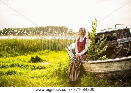 Latvian Woman In Traditional Clothing On Old Boat.