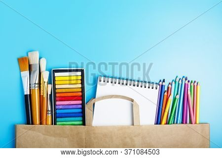 Colored Pencils, Pastels, Brushes, A White Notebook In A Paper Bag On A Blue Background. Hobby And D