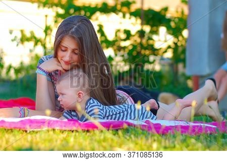 The Girl Takes Care Of A Young Boy As A Babysitter. They Both Lie On The Pink Blanket On The Grass