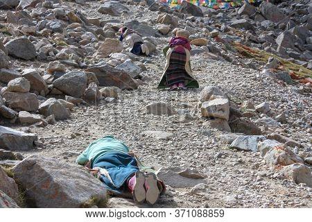 Pilgrims Prostrating On Stony Trekking Kora Around Mountain Kailash Pilgrimage Route Near Darchen, T