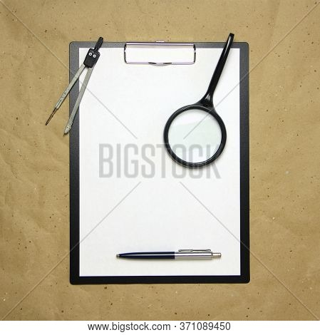 A Tablet With A White Sheet Of A4 Format With Magnifier, Pen And Divider On A Beige Craft Paper. Con