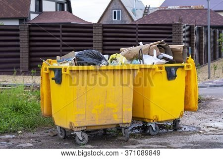 Garbage Containers Full Of Garbage. Yellow Garbage Cans Near Residential Buildings. The Concept Of E