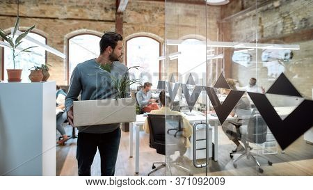 Saying Good Bye. Handsome Man In Casual Wear Holding Box With Personal Things And Leaving Modern Off