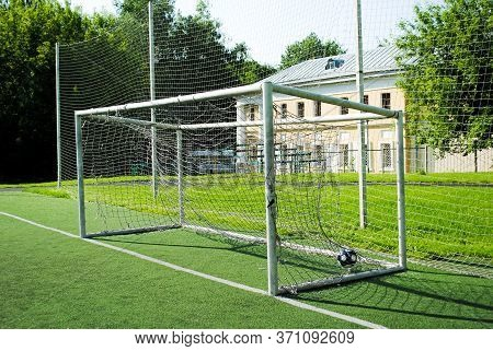A Ball In A Soccer Goal On An Amateur Soccer Field On A Sunny Summer Day. Gates With A Torn And Dirt