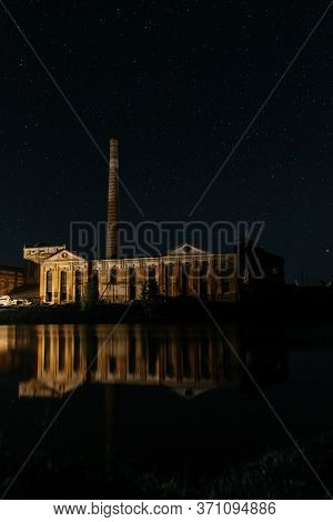Old Building With High Pipe Reflecting In Water On A Background Of The Starry Sky. Starry Night